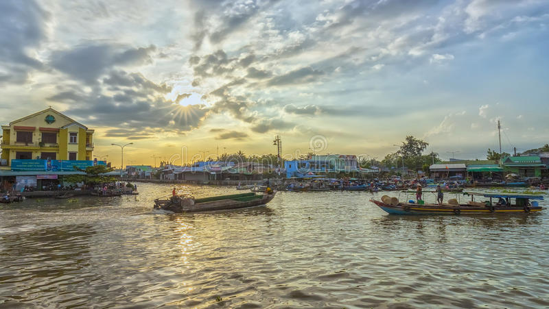 Afternoon hometown river. Soc Trang, Vietnam - February 2nd, 2016: Afternoon on river with boats homeland back and forth as sun rays radiating end of day scene royalty free stock photos