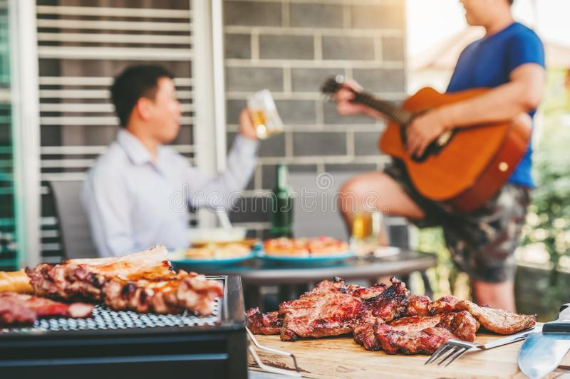 Afternoon Party Group friends enjoying drinking beer with barbecue and roast pork happy playing guitar enjoying home party stock images
