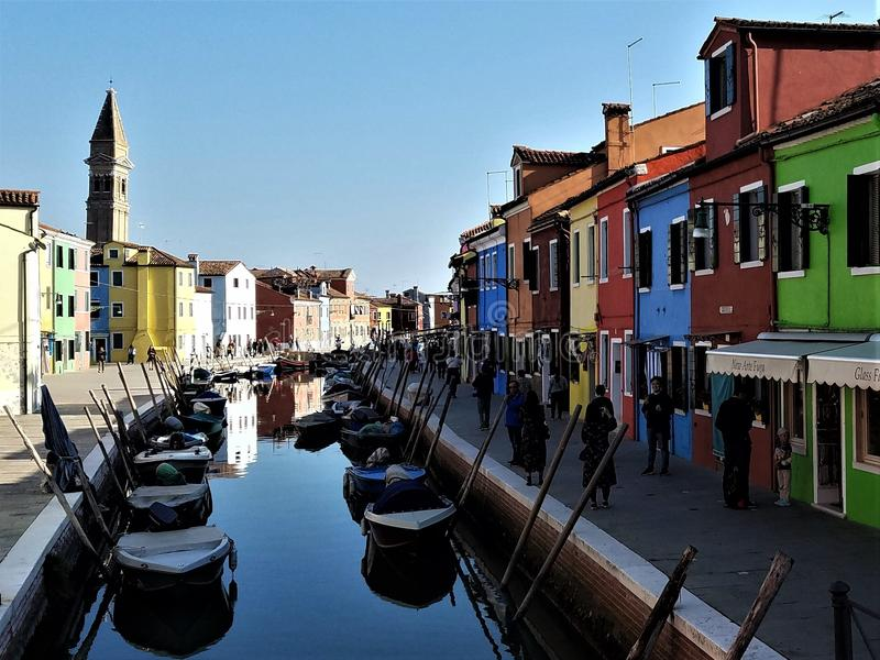 Afternoon Shadows on Burano, Italy Canal. Late afternoon sun casts shadows and reflections on a canal in Burano, Italy. Brightly colored houses line the royalty free stock images
