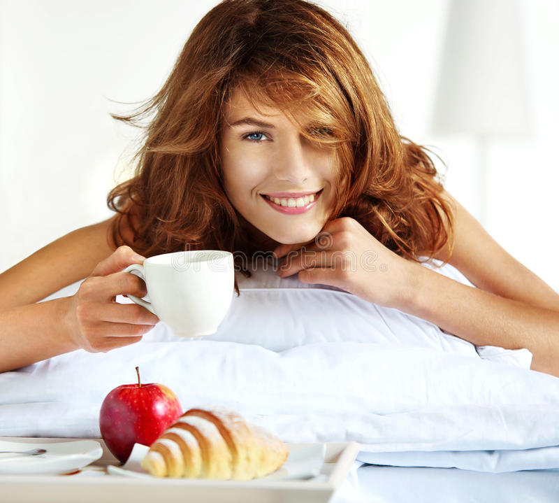 Afternoon tea in bed. Beautiful brunette woman holding white porcelain cup in hand and smiling lying in bed stock photography