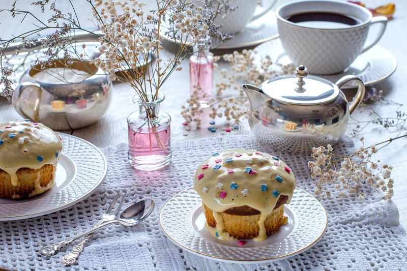 Afternoon tea with muffins. Afternoon tea. Cupcakes with frosting. White cups and saucers. Silverware. Vases with flowers. A beautiful table setting. Selective royalty free stock image