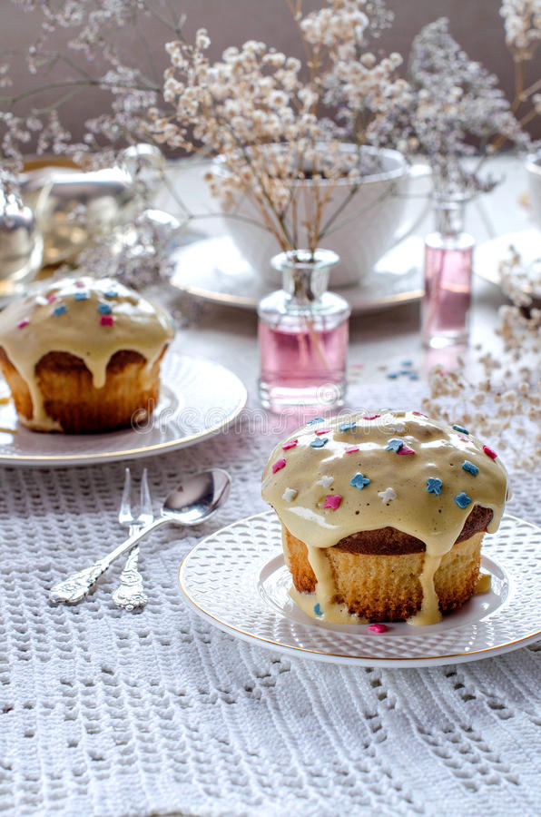 Afternoon tea with muffins. Afternoon tea. Cupcakes with frosting. White cups and saucers. Silverware. Vases with flowers. A beautiful table setting. Selective royalty free stock photo