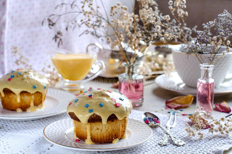 Afternoon tea with muffins. Afternoon tea. Cupcakes with frosting. White cups and saucers. Silverware. Vases with flowers. A beautiful table setting. Selective royalty free stock images