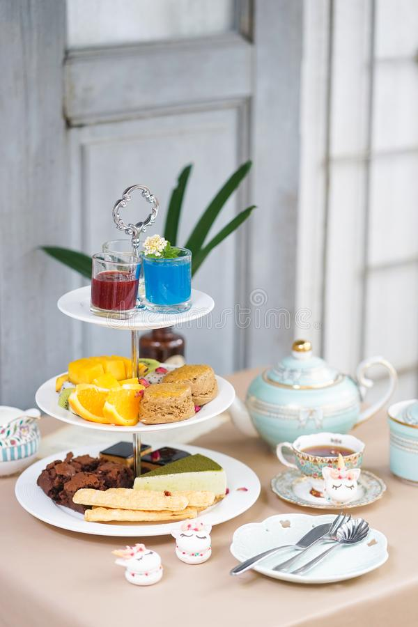 Afternoon tea. Tea party with unicorn macarons, scones, bakeries stock photo