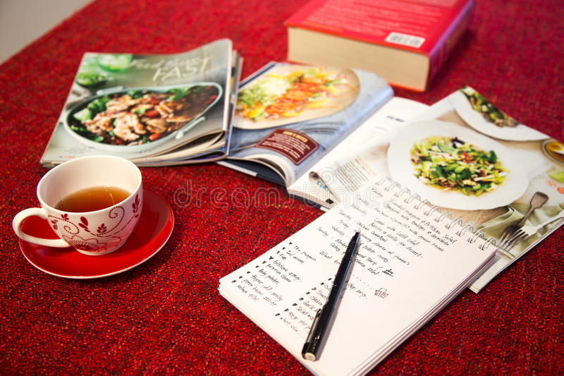 Afternoon Tea. Preparing recipe and shopping list while enjoying a cup of tea in the afternoon, using cooking magazine as inspiration stock image