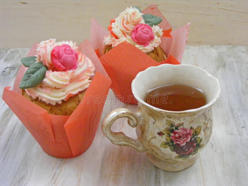 Afternoon tea with roses cupcakes in vintage teacup on shabby table colors of spring royalty free stock image