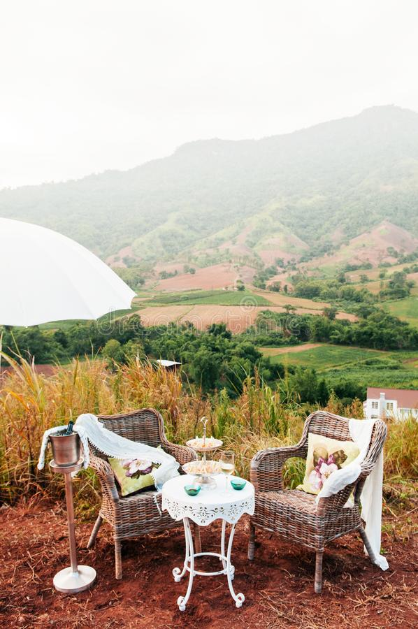 Afternoon tea vintage picnic set on hill with mountain view stock photography