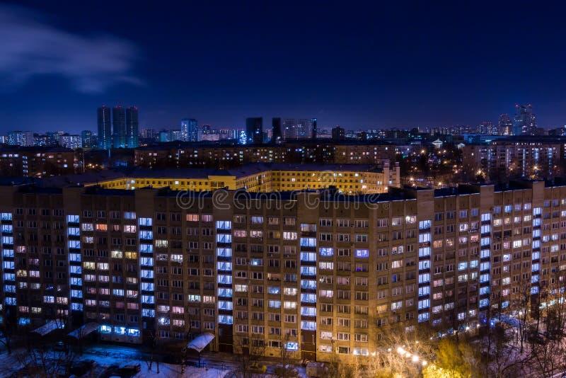 Afton- eller nattstadslandskap Ljus i Windows av hyreshusar royaltyfri fotografi