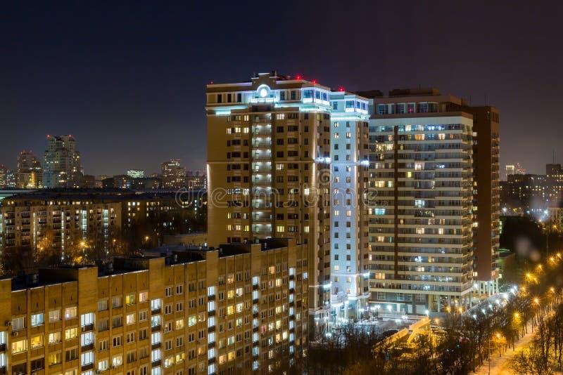Afton- eller nattstadslandskap Ljus i Windows av hyreshusar royaltyfria foton