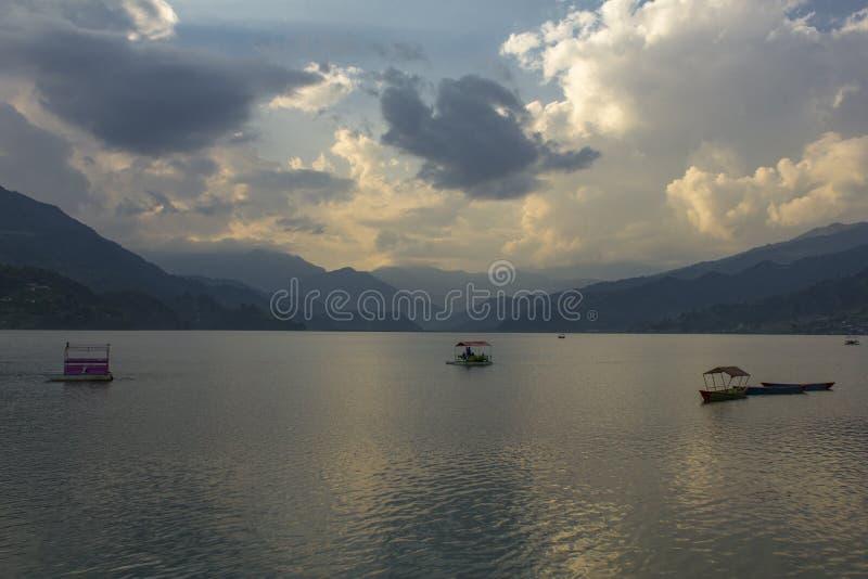 Afton sjö Phewa med katamaran på bakgrunden av en bergdal i dimman och aftonhimlen royaltyfria foton