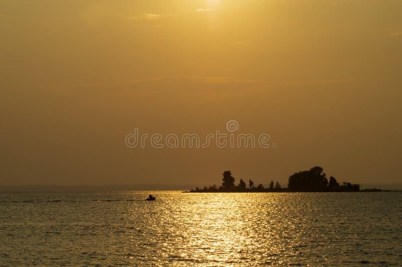 Aftonbakgrund, havssikt med solkatten på vattenyttersidan royaltyfri fotografi