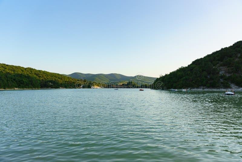 Aftonfolkrodd och katamaran på cypress sjön Inställningssolen har färgat berglutningarna med ljus royaltyfri fotografi