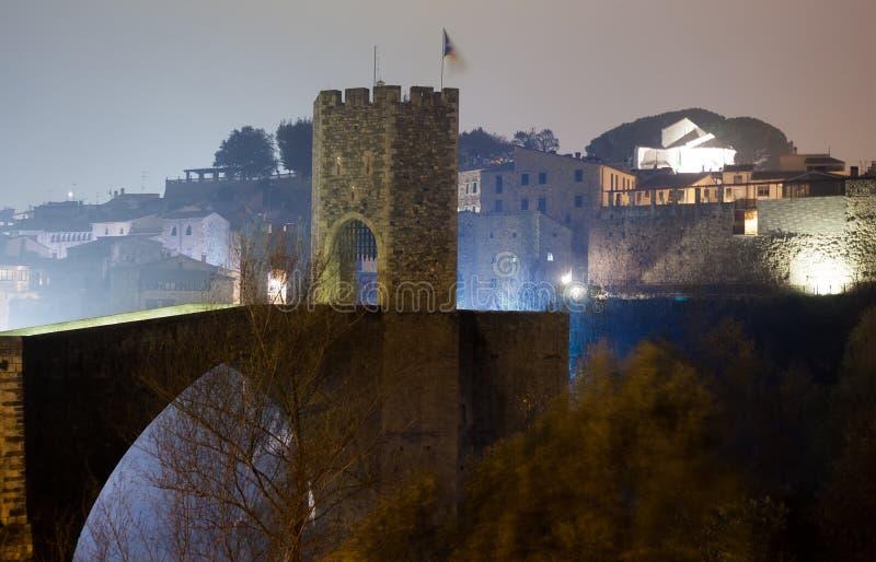 Aftonfoto av den medeltida bron med stadsporten Besalu Catalo arkivfoto