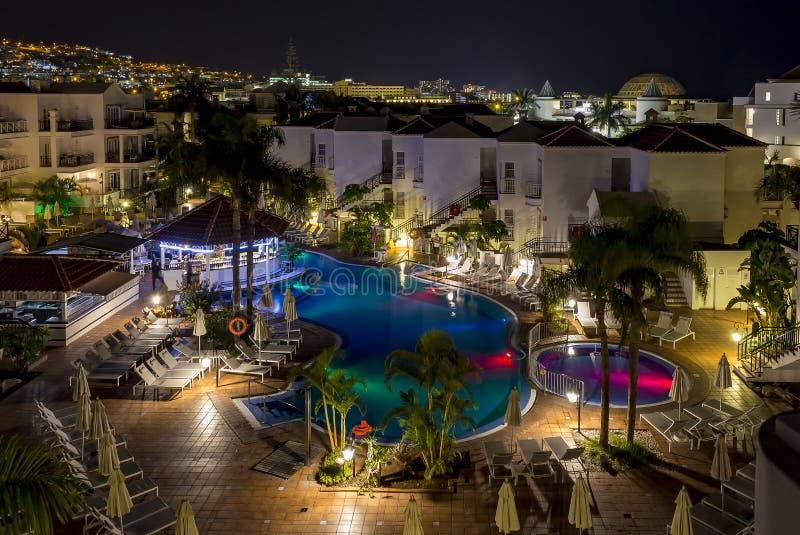 Aftonfoto som förbiser de färgrika tända hotellen och en simbassäng i Costa Adeje, Tenerife, Spanien royaltyfria bilder