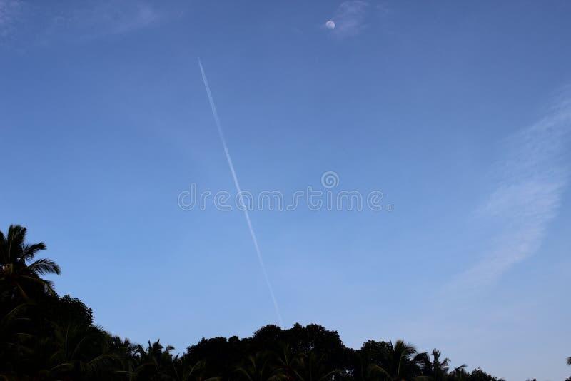 Aftonhimmel med ett strålflygplan och måne royaltyfria foton
