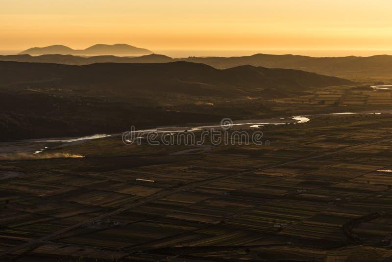 Aftonlynnepanorama som tas från den Byllis byn - flyg- sikt av landskapet med fält, flodmusikbandet och berg i bakgrunden arkivfoto