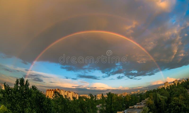 Aftonregnbåge i himlen över staden på solnedgången i sommaren, i regnet royaltyfria bilder