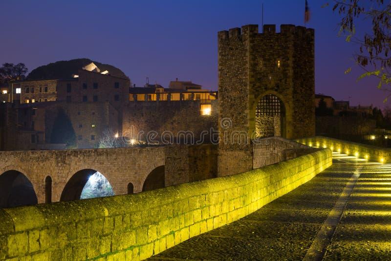 Aftonsikt av den medeltida stenbron med porten Besalu royaltyfri bild