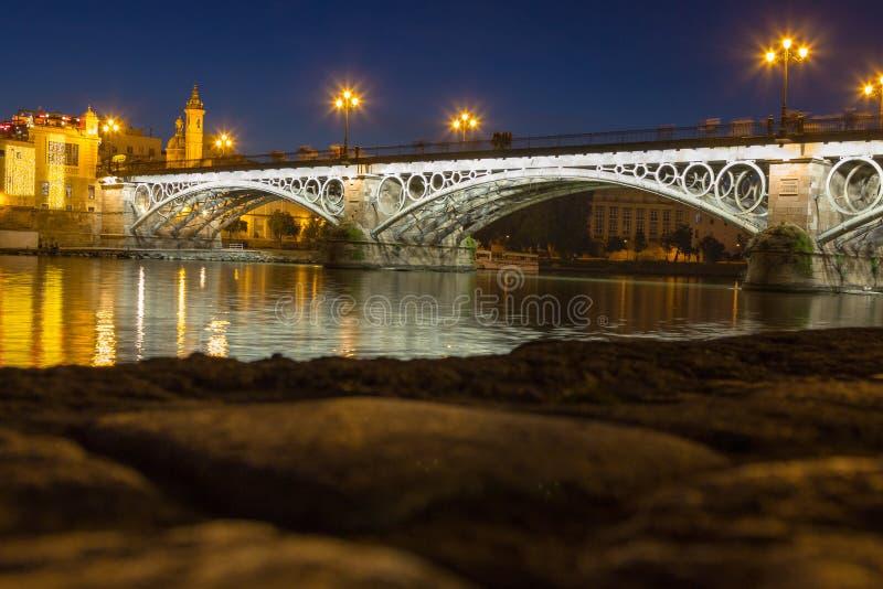 Aftonsikt av den Triana bron i Seville arkivfoto