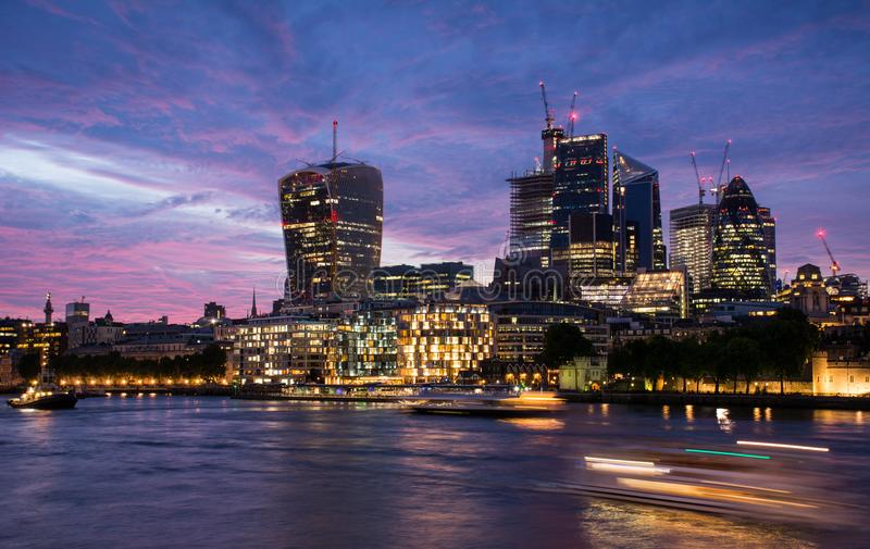 Aftonsikt av skyskraporna i staden, ett finansiellt område i London, Förenade kungariket, med flodThemsen royaltyfri foto