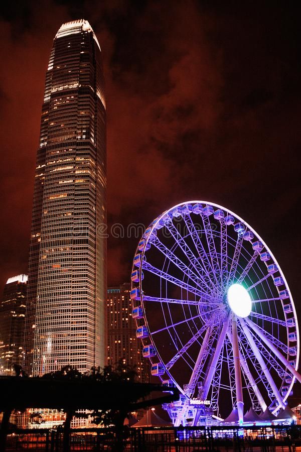 Aftonsikt från invallningen till pariserhjulen med ett höghus Hong Kong arkivfoton