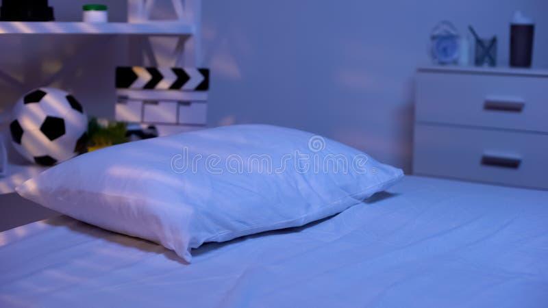 Aftonskymningsovrum av den tonårs- pojken, bekväm sänglinne, hemtrevlig sömn arkivbilder
