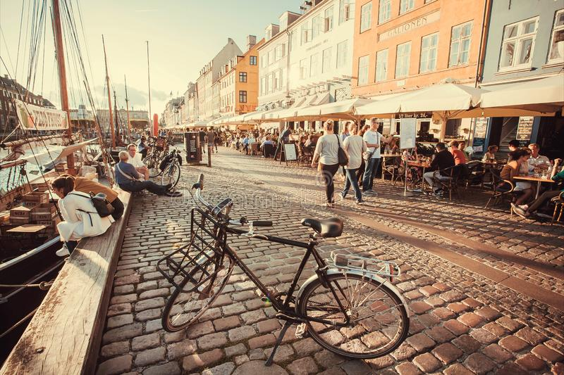 Aftonsol på den Nyhavn flodstranden med att gå folk och att koppla av i restauranger av populärt stadsfritidområde arkivbild