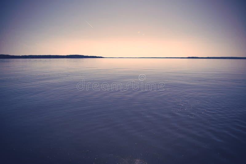 Aftonsolnedgång över en sjö royaltyfri foto