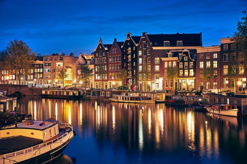 Aftonstad Amsterdam i Nederländerna på banken arkivbilder