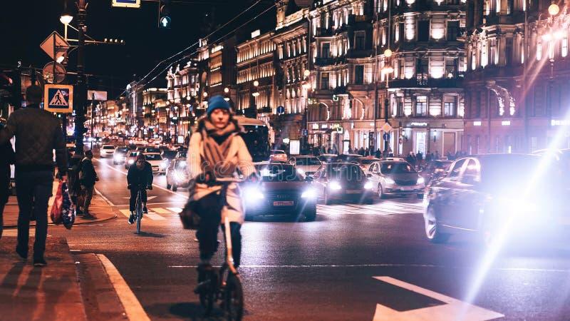 Aftonstad med bil- och folktrafik fotografering för bildbyråer
