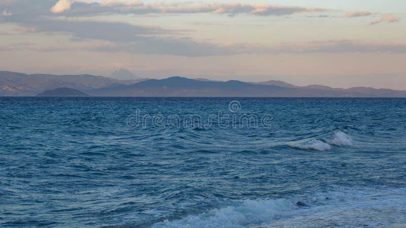 Aftonstorm på det blåa havet som förbiser himlen och bergen royaltyfri foto