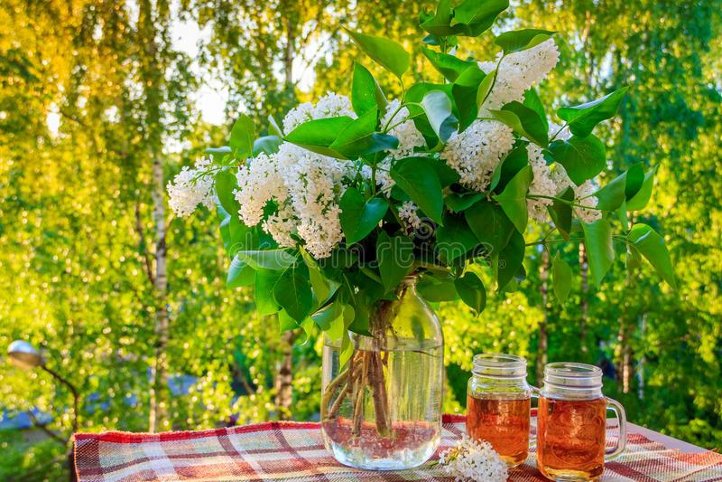 Aftontebjudning på balkongen Exponeringsglas med te och en bukett av lilan Aftonsommarte royaltyfri foto
