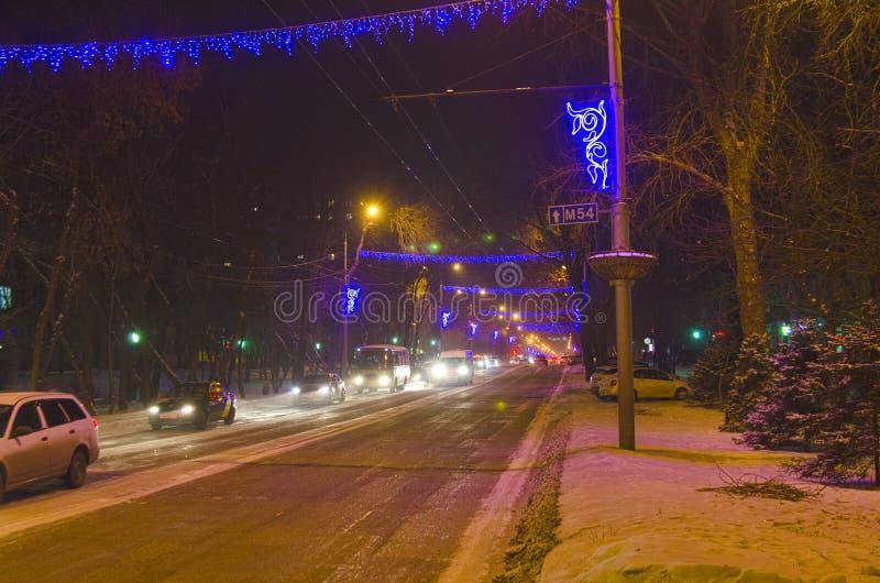 Aftonvinterstad i ljuset av lyktor för gatabelysning Gatan dekoreras för det nya året royaltyfri foto