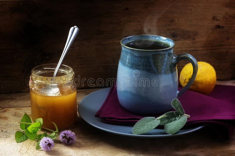 Aftreksel tegen koude met verse salie, munt, honing en citroen stock afbeeldingen