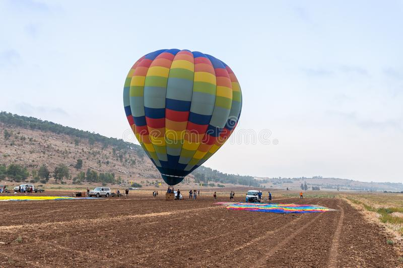 Pilots of a striped air hot balloon are preparing to fly out at the festival of ais hot balloons. Afula, Israel, 3 August, 2018 : Pilots of a striped air hot stock photo