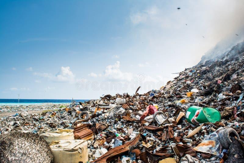 Afval bij het hoogtepunt van de huisvuilstortplaats van rook, draagstoel, plastic flessen, vuilnis en afval bij tropisch eiland stock afbeelding