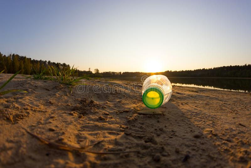Afval op strand, plastic fles op zand met overzees en golf royalty-vrije stock afbeeldingen