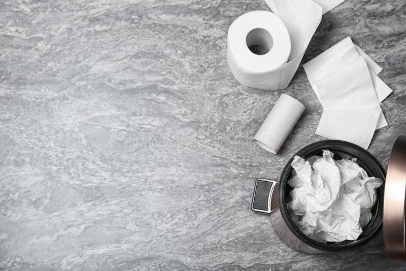 Afvalbak met gebruikt toiletpapier en nieuw broodje op grijze achtergrond, hoogste mening royalty-vrije stock afbeeldingen