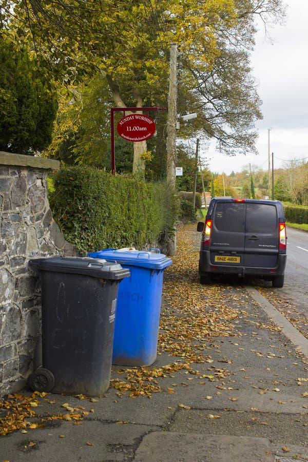 Afvalbakken die op inzameling buiten Drumbo-Parochiekerk wachten in de Provincie onderaan dorp van Drumbo in Noord-Ierland stock foto
