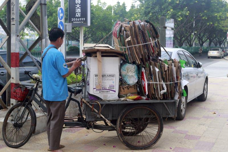 Afvalinzameling door driewieler stock afbeelding