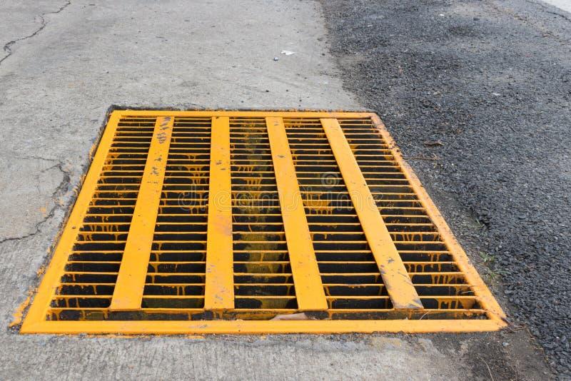 Afvoerkanaal van de dekking van de metaalrooster in gele kleur rond met ruw aspis stock foto