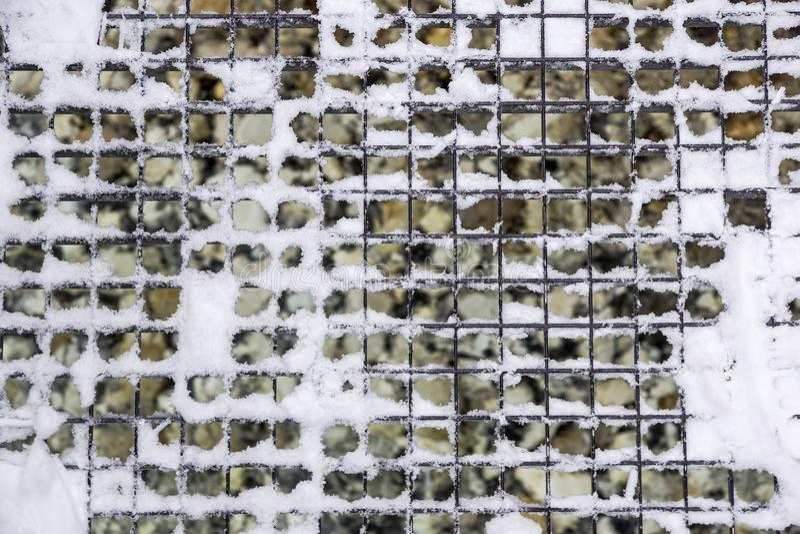 Afvoerkanaalrooster voor waterdrainage in stadsstraten, metaalnet, ijzermangat, met sneeuw tijdens een onweer wordt behandeld, bl royalty-vrije stock afbeeldingen