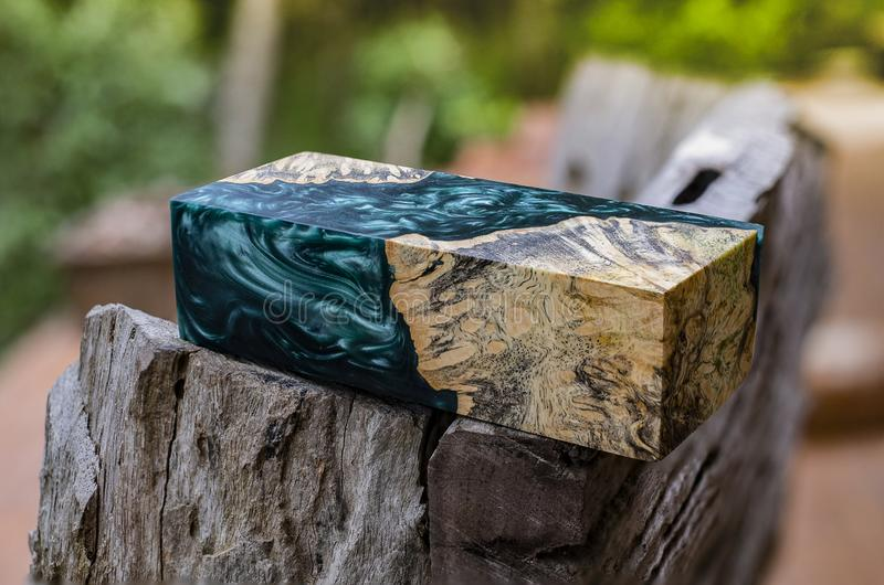 Afzelia burl wood bar casting with epoxy resin Stabilizing for blanks. On blurred background royalty free stock photos