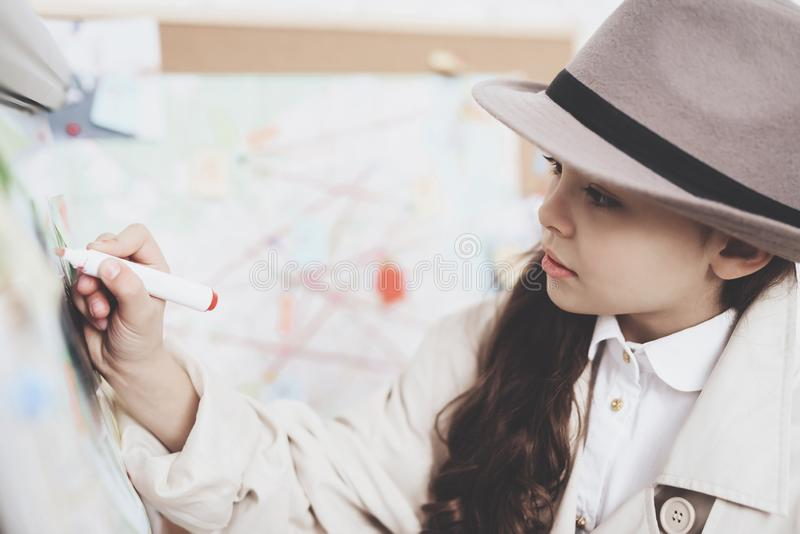Agência de detetive privado A menina está tirando com o marcador na placa dos indícios foto de stock