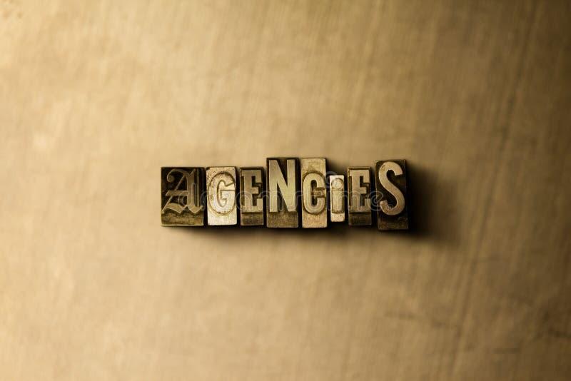 AGÊNCIAS - close-up vintage sujo da palavra typeset no contexto do metal ilustração stock