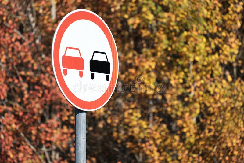 Against the background of the autumn forest road sign overtaking is prohibited. Autumn day stock photos