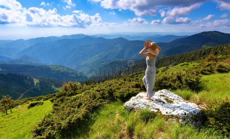 Against the background of beautiful mountain scenery with sun rays and cloudy sky the girl is staying in long dress, straw hat. stock images