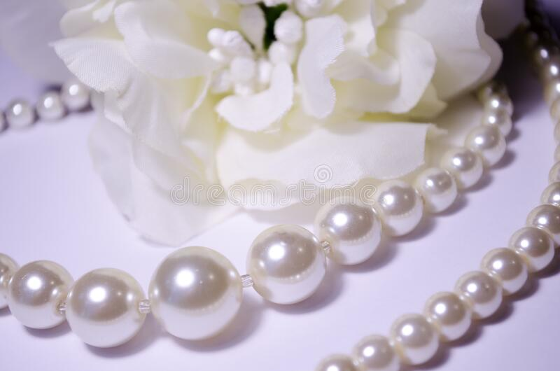 Against the background of a flower. White pearl jewelry. Luxury jewelry for women and girls. Pearl necklace. Artificial pearls. Snow-white pearls on a white stock image