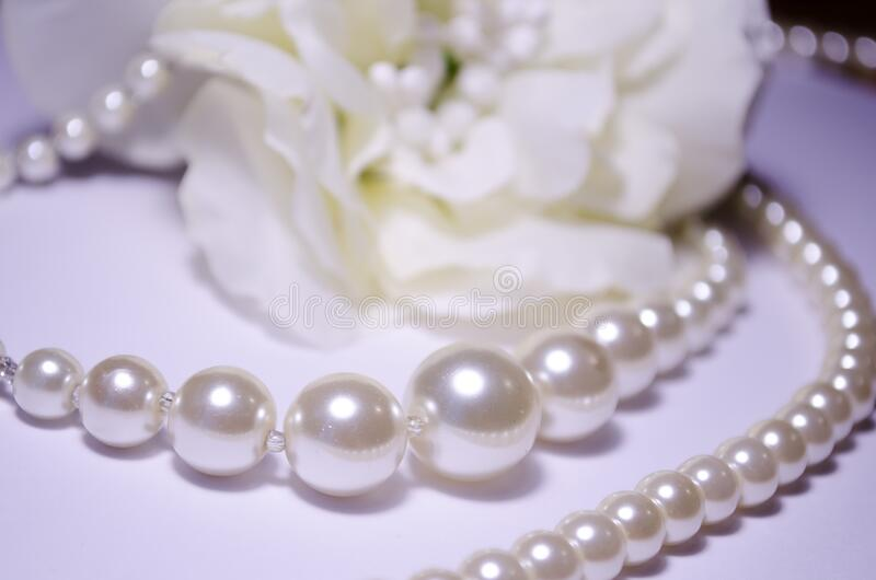 Against the background of a flower. White pearl jewelry. Luxury jewelry for women and girls. Pearl necklace. Artificial pearls. Snow-white pearls on a white stock photos