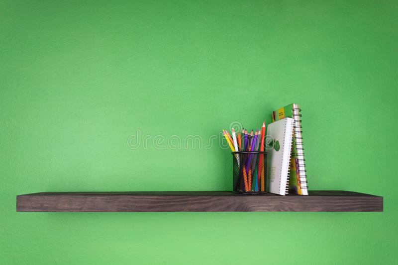 Against the background of a green wall a dark shelf with the texture of wood on which is installed a glass with colored pencils on. It were supported by two royalty free stock image